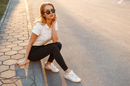 Young woman hipster in stylish sunglasses in a white polo shirt in black jeans in white fashionable sneakers sits on the asphalt against the background of a summer sunset. Pretty girl resting. Stok Fotoğraf