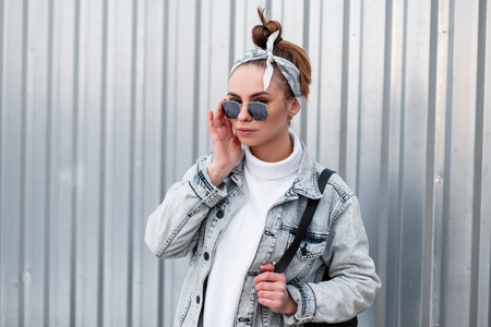 Stylish attractive young hipster woman in a stylish bandana in trendy sunglasses in a summer jacket with a backpack in a sweater near a metal wall. American girl. Summer style clothes. Stock Photo