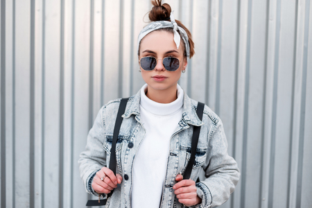 Fashionable modern young woman hipster in a bandana with a stylish hairstyle in a denim jacket in trendy sunglasses with a black backpack in a sweater posing near a metal wall. Attractive girl. Stock Photo