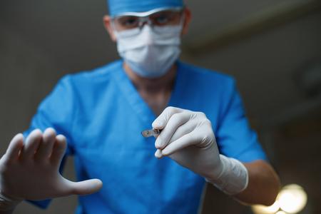 Plastikarzt in medizinischer Spezialkleidung in Schutzbrille in einer Maske in Handschuhen hält im Operationssaal ein Skalpell in der Hand. Moderner Chirurg beginnt die Operation. Standard-Bild