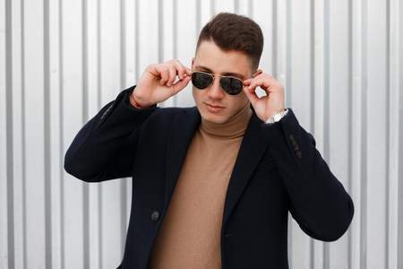 Stylish serious young hipster man in stylish sunglasses in a beige knitted sweater in a fashionable jacket poses and looks into the camera on the street near the silver wall. Handsome guy. Фото со стока