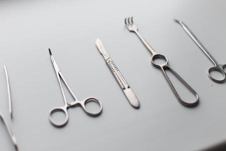 Ensemble d'instruments médicaux en métal (lame de scalpel, ciseaux, forceps, pinces, forceps) sur fond blanc dans la pièce. Outils chromés professionnels modernes.