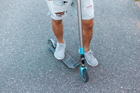 Young guy riding a scooter. Mens feet in denim ripped stylish shorts in white sneakers. Close-up.