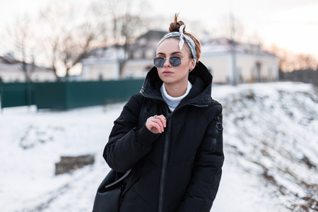 Young stylish beautiful hipster woman in black sunglasses in a stylish bandana in a trendy black jacket with a backpack poses outdoors on a background of snowy hills. Fashionable beautiful girl.