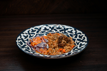 Juicy hot delicious pilaf with beef with onions and beef in Georgian restaurant. National dish of oriental cuisine. Dinner time.