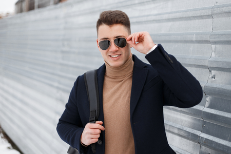 Joyful young hipster man in black sunglasses in a stylish knitted sweater with a black backpack in an elegant coat posing beside a shiny metal fence. Happy guy enjoying the weekend. Stock Photo