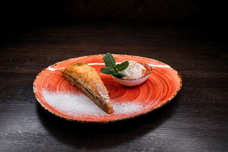 Turkish baklava with pistachios and vanilla sweet ice cream decorated with fresh mint leaves. Traditional Oriental cuisine. Stockfoto