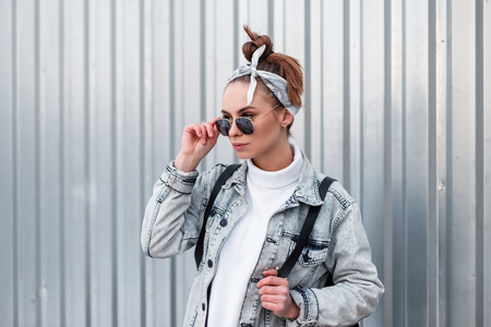 Beautiful attractive young hipster woman in a stylish bandana with a stylish hairstyle in fashionable sunglasses in a summer denim jacket with a backpack near the metal wall. Modern American girl. Stock Photo