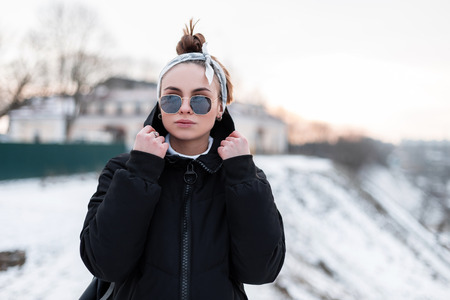 Cute young hipster woman in stylish black sunglasses in black trendy winter jacket with a leather backpack with a bandana walks on a winter day and enjoy the weekend. Cute girl.