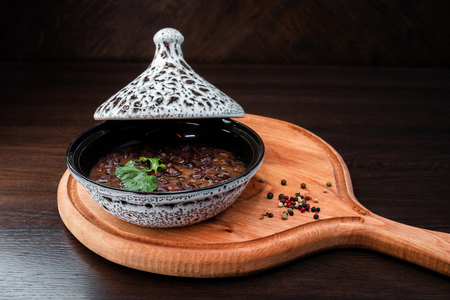 Hot snack Lobio In Georgian with celery in a ceramic pot at an oriental restaurant. National dish. Stock Photo