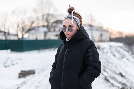 Amazing young fashionable hipster woman with a stylish hairstyle with a stylish bandanna in fashionable sunglasses in a winter black coat for a walk outdoors on a winter day. Modern stylish girl.