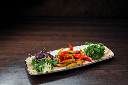Yellow and red pickled peppers garnished with fresh arugula and parsley. Traditional tasty snack for lunch.