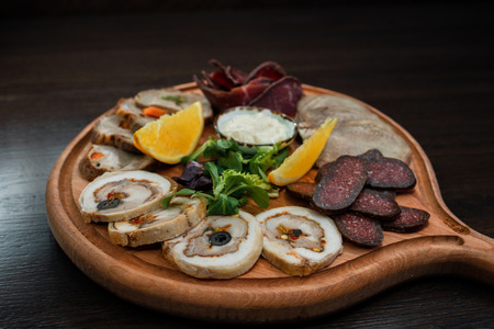 Meat platter: chicken roll, jerky, salami sausage, pork. Dish is decorated with fresh orange slices, sauce and herbs.