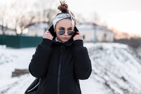 Attractive young hipster woman in stylish black sunglasses in black trendy winter jacket with a leather backpack with a bandana walks on a winter day and enjoy the weekend. Cute girl.