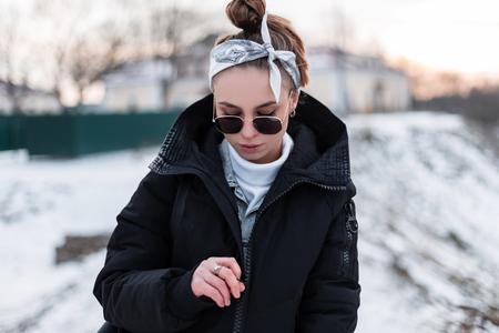 Young hipster woman in black sunglasses in a black winter coat with a stylish leather backpack with a bandana in a white sweater walks outdoors on a winter day and enjoys the weekend. Beautiful girl.