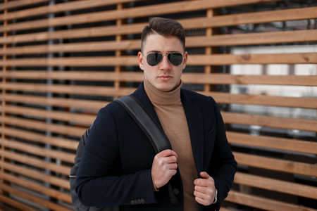 3cfa4743090 American serious young hipster man in an elegant coat in a knitted sweater  with a stylish