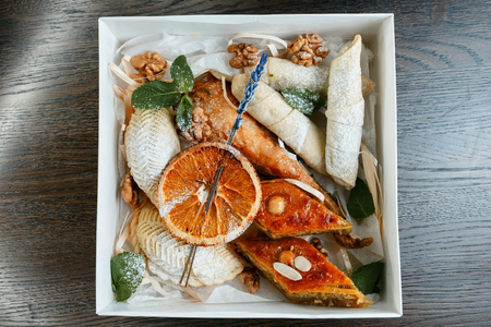 """Eastern sweets: """"Baklava"""" with walnuts, """"Shekerbur"""" with nuts, """"Baklava"""" Turkish with pistachios with an oriental bagel in a white box, decorated with lavender and mint leaves. Great addition to tea."""