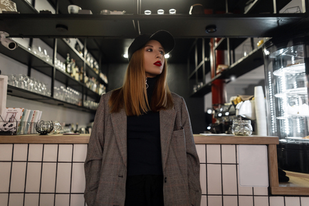 Amazing young woman in a stylish black cap in a gray vintage jacket in retro style with a pierced nose with beautiful makeup with red lips is standing on the background of the bar counter. Modern girl Stock Photo