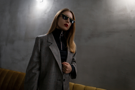 Young attractive hipster woman in unusual stylish glasses in a vintage elegant checkered jacket in a black stylish shirt with red lips with an earring in her nose stands in the cafe. Stylish girl.