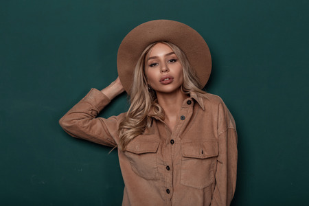 Portrait of a secular young blonde woman with curly hair in a stylish elegant hat with natural beautiful makeup in a vintage fashionable shirt near the background of a green wall. American glamor girl