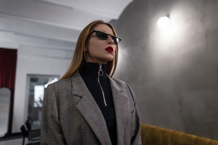 Amazing beautiful stylish young hipster woman in black trendy sunglasses in gray stylish checkered jacket with red lips with pierced nose posing in a cafe. Modern girl. Womens fashion in retro style.