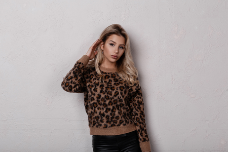 Slim glamorous young woman with long blond curly hair in a stylish leopard sweater in fashionable black leather pants posing in the studio near a white wall. Charming stylish girl. Women's fashion.