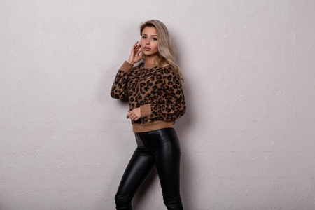 Slim  glamorous young woman in a beautiful stylish leopard sweater in fashionable black leather pants poses in a studio near a white wall. Charming stylish girl. 写真素材