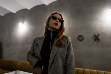 Unusual amazing young hipster woman in trendy checkered jacket in retro style in trendy sunglasses with pierced nose with red lips posing in a cafe on a background of a vintage gray wall. Modern girl