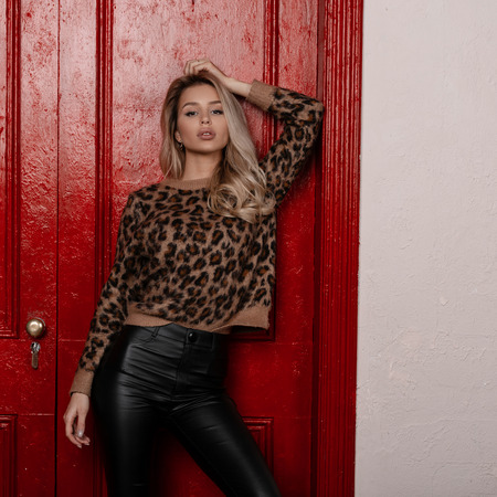 Cheeky modern young blonde woman in a beautiful stylish leopard sweater in black leather pants poses indoors near red vintage doors. Sensual attractive girl. Women's fashion. Foto de archivo - 117832347