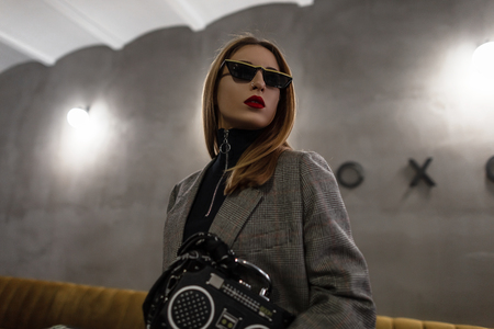 Modern hipster young woman in stylish sunglasses with a red-lips nose-ear in a checkered gray stylish jacket with a black bag in the form of a tape recorder standing indoors. Stylish future girl. Stock Photo