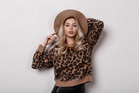 Beautiful pretty young woman in a trendy stylish leopard sweater in trendy black leather pants and a beige hat posing indoors on a white background. Cute stylish blonde girl. Womens fashion.