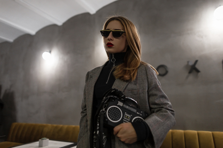 Stylish young woman hipster in sunglasses in retro style with an earring in the nose with red lips in a gray checkered stylish jacket with a vintage bag recorder stands in a cafe. Modern girl.