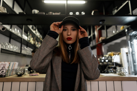 Stylish young woman with a pierced nose in a trendy black cap in a gray vintage checkered jacket with red lips posing at the bar. Modern fashionable girl. Women's clothing in retro style.