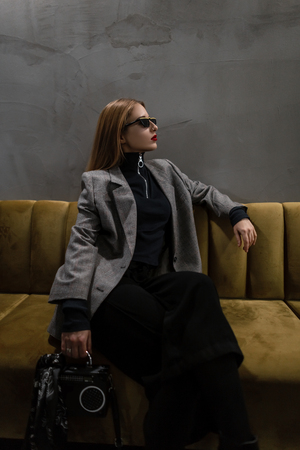 Modern stylish young hipster woman in stylish elegant checkered jacket with vintage black handbag in the form of tape recorder in black pants poses sitting on the sofa in the studio. Trendy girl. Stock Photo