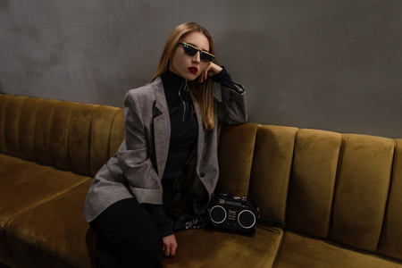 Amazing hipster young woman with red lips with a pierced nose in a checkered jacket in retro style with a fashionable bag-recorder sitting on the sofa in a cafe. Attractive old fashioned punk girl. Stock Photo