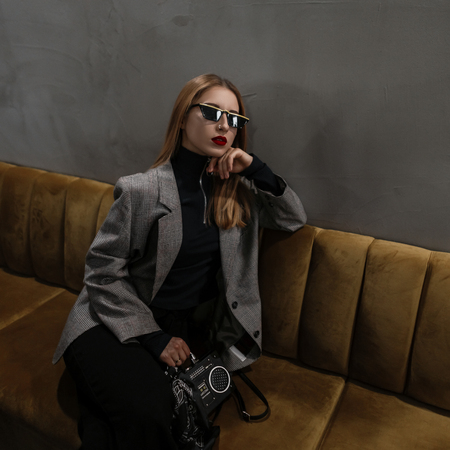 Modern hipster young woman with a pierced nose with red lips in a vintage gray checkered jacket in black trousers with a stylish handbag-recorder sits on a sofa in the room. Amazing old-fashioned girl