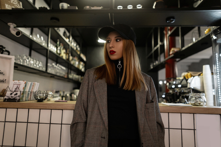 Modern amazing young woman with a pierced nose in a fashionable black cap in a gray vintage checkered jacket with red lips is standing in a cafe on the background of a bar counter.Attractive girl. Stock Photo