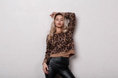 Sexy stylish young woman with curly blond hair in fashionable leopard sweater in fashionable black leather pants posing in a studio near a white wall. Charming sensual girl. Women's stylish clothing.
