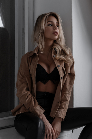 Gorgeous sexy young blond woman with curly hair in an elegant lace black sconce in leather trendy pants in a stylish shirt sitting near the window in the room. Beautiful charming sensual girl.