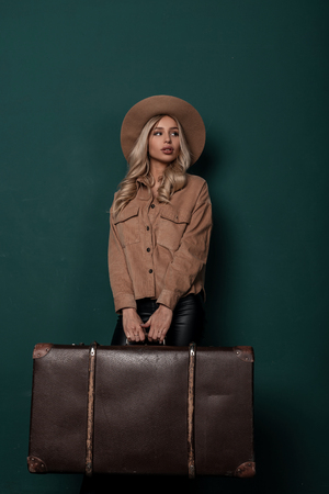 Beautiful young blond woman in a beige elegant hat in a stylish shirt in leather pants is standing and holding a vintage brown leather suitcase in retro style. Nice girl gathered on a trip on studio .