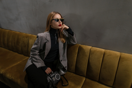 Nice hipster young woman with a pierced nose with red lips in a vintage retro-style jacket in black trousers with a trendy bag-recorder sits on a sofa in a cafe. Attractive old-fashioned punk girl. Stock Photo