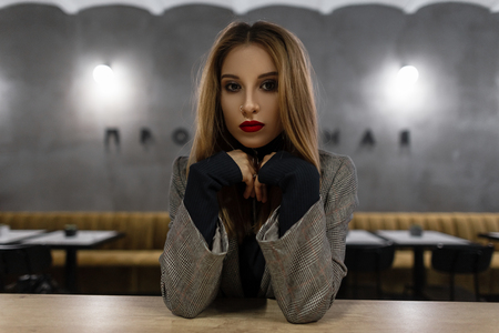 Amazing pretty young woman with beautiful make-up with red lips with a pierced nose in a gray vintage checkered jacket in a black t-shirt  sits at a table in a cafe. Stylish cute girl model.