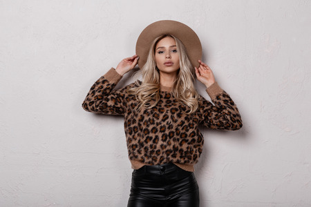 Charming stylish young woman in a vintage stylish leopard sweater in black leather pants in a luxurious hat posing indoors near a white wall. Modern glamorous girl blonde. Stock Photo