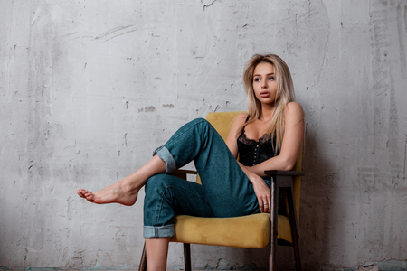 Attractive sexy young woman with blond hair with natural make-up in a black lace sconce in stylish jeans posing on a vintage chair in the studio. Sensual charming girl.