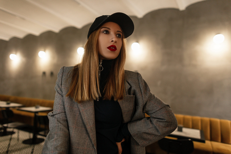 Model pretty young woman in a trendy checkered jacket in retro style in a fashionable black cap with a pierced nose with red lips posing in a cafe on the background of an old gray wall. Modern girl