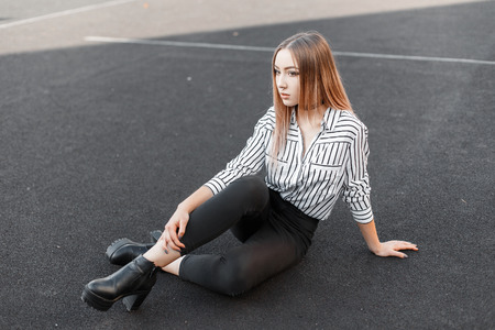 Cute young woman in a stylish black and white striped shirt in black jeans in leather shoes with a pierced nose sits on the stadium on a sunny warm summer day. Pretty girl teenager resting outdoors.