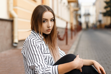 Pretty attractive young woman in a vintage black and white striped blouse in stylish jeans with elegant velvet necklaces sits in the city on a warm spring day. Beautiful girl relaxes outdoors. Stock Photo