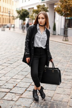 Young woman with a pierced nose in a spring jacket in a striped blouse in black jeans in leather shoes with a black handbag walks in the city near vintage buildings in the spring day. Teenager girl.