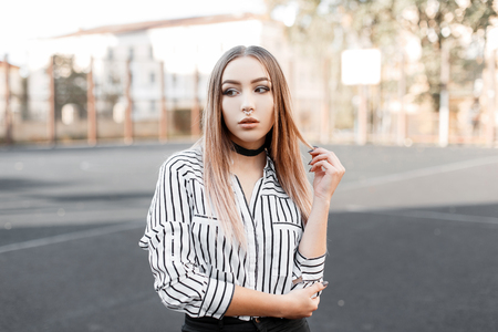 Cute young teenager woman with a pierced nose in a fashionable striped shirt in black jeans with a black velvet necklace stands outdoors on a spring sunny day. Pretty modern girl model on the walk