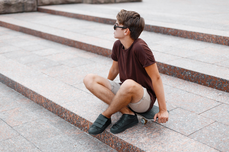 Fashionable young hipster man in black sunglasses in a vintage t-shirt in trendy shorts in sneakers resting while sitting on a skateboard in the city on a summer day. Modern American guy on vacation.